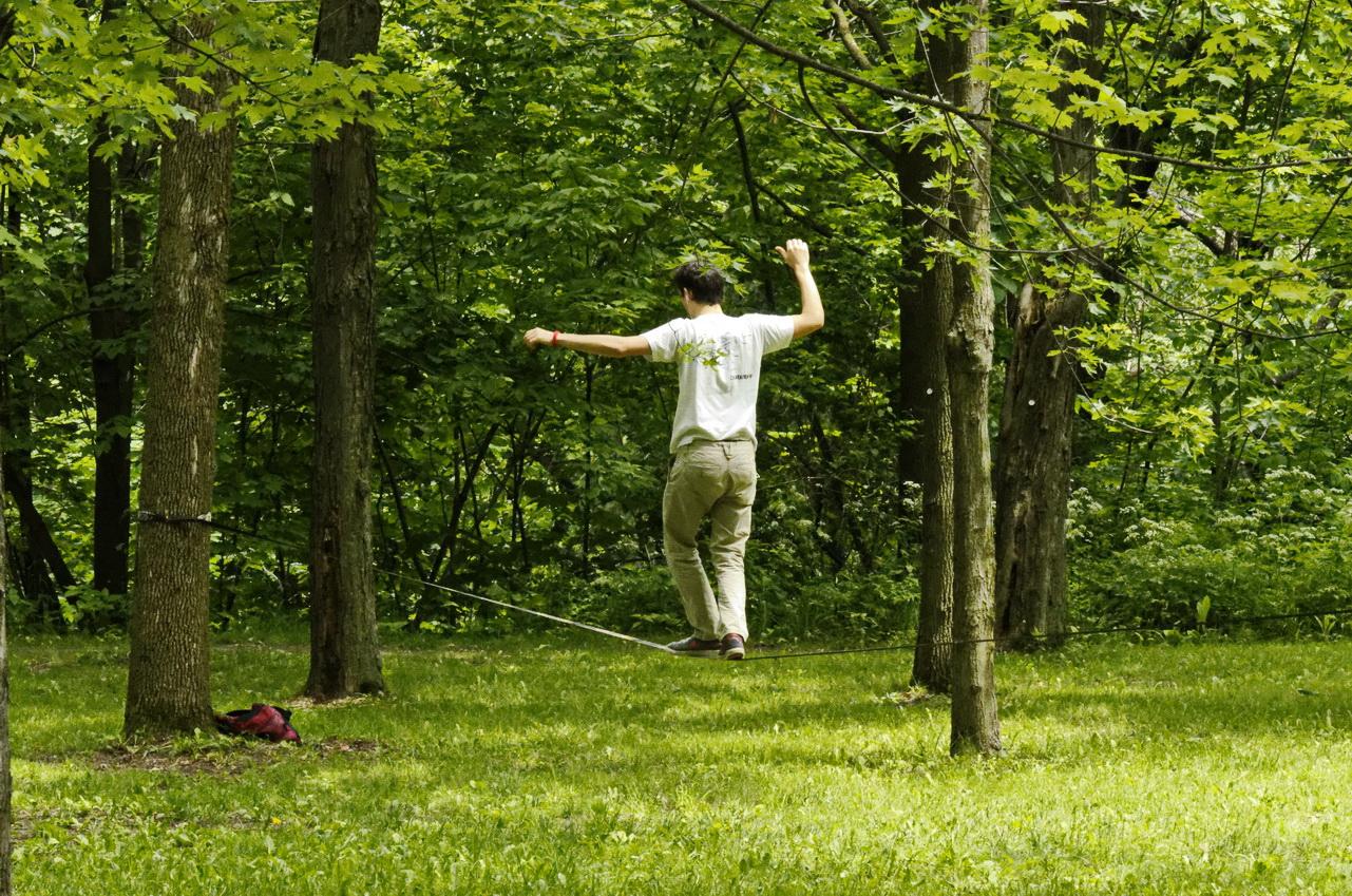 Homme s'entraînant à la slack line en forêt.